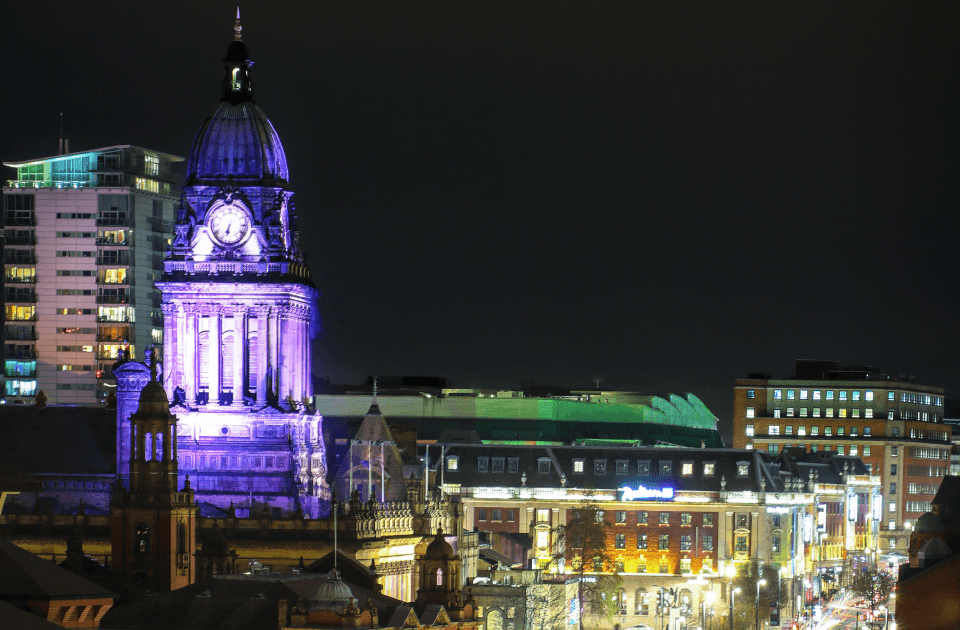 City scape of Leeds City Centre at night with Leeds Town Hall clock tower lit up purple.
