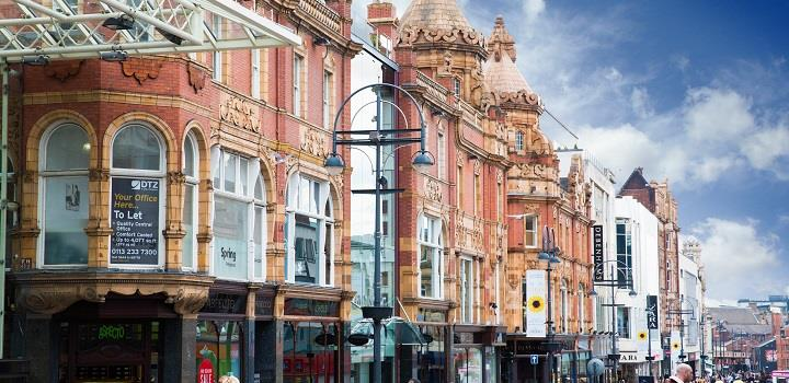 Leeds Briggate in the daytime with a blue sky.